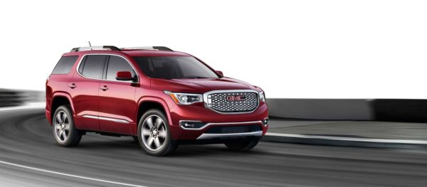 A red 2017 GMC Acadia Denali driving down a road