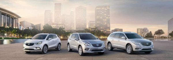 Three Buick SUVs lined up against a city skyline