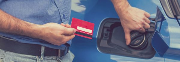 A man holding a credit card near a gas tank featured in a blog post about gas mileage